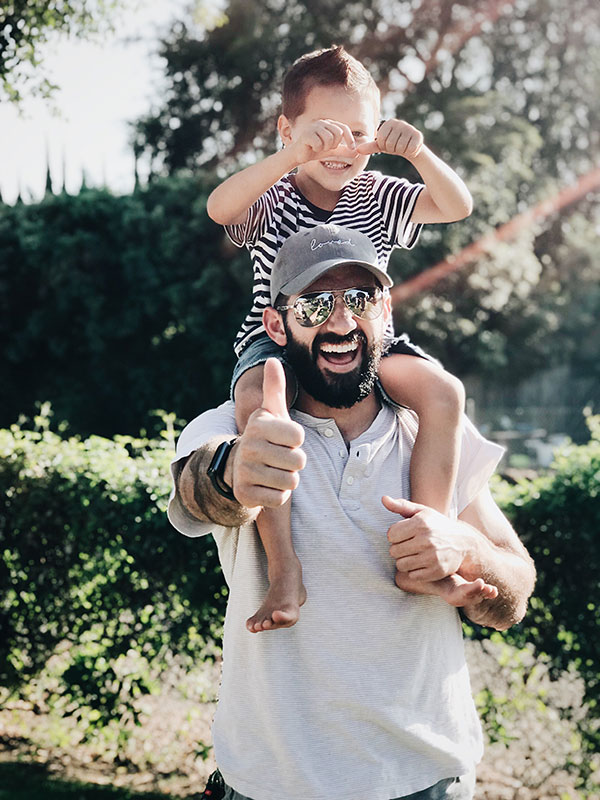 man-holding-a-child--while-smiling