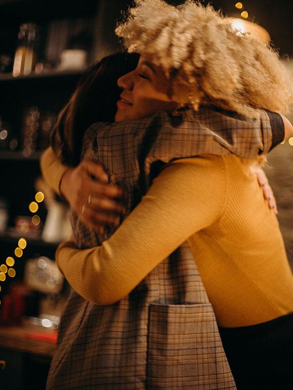 two-women-hugging-at-night